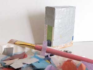 Decoupage the small cardboard boxes with recycled paper