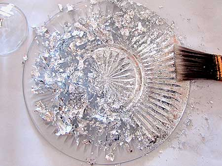 brushing the metal leaf onto the back of the plate - How To Make Mercury Glass