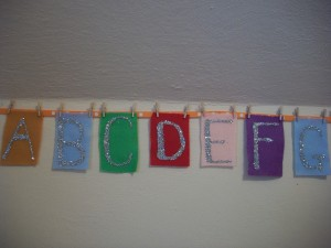Hang the alphabet on a ribbon using miniature craft clothespins and then nail the ribbon to the wall.