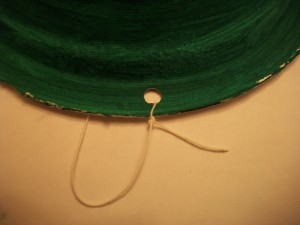 Tie the ends of your string through each hole, leaving enough slack to go under your child's chin.