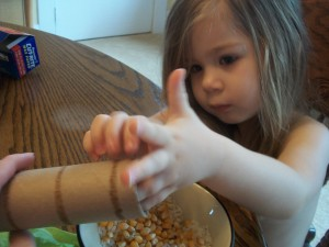 Have your kiddo help you pour in rice, popcorn kernels, or whatever you've decided to use to make your sound effects.