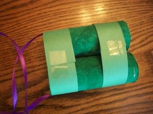 Wrap your construction paper strips around so they overlap on the back, and tape them in place.