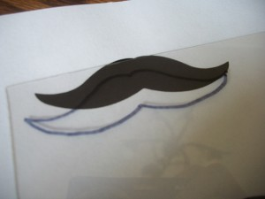 Trace the shape of a mustache onto your shrink film. (We printed some from the Internet.)