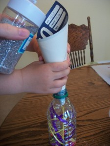Put your ribbons, buttons, sequins, beads, dice, or whatever in the bottle.  Add some glitter and fill with water.