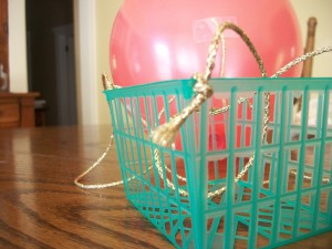 Tie one end of each string to a corner of your basket (or tape them to your milk carton).