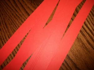 Cut your paper lengthwise into strips. The width is up to you. We did 11 strips for pumpkin craft.