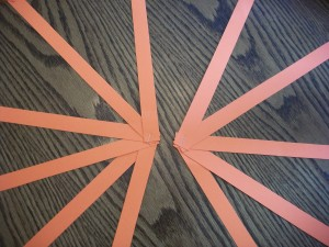 Fan the strips out and staple them at the gathering point. Then tape the two fans together.