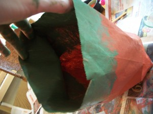 Paint the top quarter of the paper bag green, both on the outside and the inside.