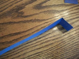 Fold each of the construction paper legs about an inch from one end.