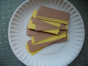 "To make your lion's mane, cut yellow and brown construction paper into short strips.  Ours are about 1"" by 3""."