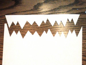 Cut out two rows of jagged monster teeth from white construction paper or craft foam.  (Craft foam will hold up way better.)
