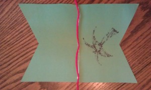 Add some glue along the inside fold and lay your yarn down. Fold each flag over and glue in place.