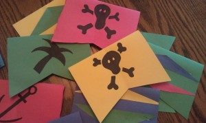 Decorate your flags with a pirate theme. You could print out clip art to glue on or just draw them on like we did. We went with ships, anchors, palm trees, and of course, the skull and crossbones.