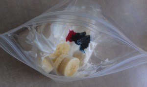 Put about one half cup of yogurt, one half a sliced banana, and three drops of food coloring in a zip bag.