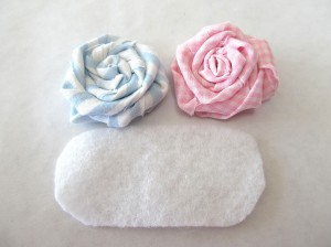 Cut a piece of felt that is slightly smaller than both of the rosettes Glue your rosettes onto the felt, and set aside.