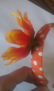 Hot glue one or more silk flowers to the wrapped headband.