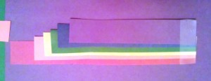 Cut equal strips from each color of construction paper.  Trim the end of each color to be a bit shorter than the previous one.