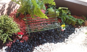 If your container is large enough, you can make different scenes in your fairy garden.  Here is our park bench scene.