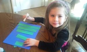 Cut five green strips (ours were about 1 1/4' wide) at varying lengths.  Then have your little one glue them onto a background color in ascending order by size.