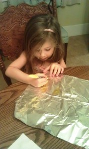Draw flames onto your aluminum foil with the yellow marker and fill them in.