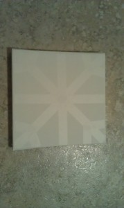 Lay the canvas down and use the tape to make a snowflake pattern like the one in the picture.  It's basically an X with an extra horizontal stripe through the middle.  Then add small pieces of tape at the corners.