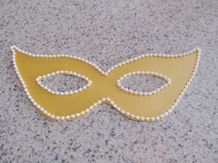 Closeup of gluing the decorations onto the mask