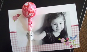 Use your sharp blade to cut slits in the photo at the top and bottom of the child's hand and then slide the lollipop stick through so it looks like your kiddo is offering it right off the picture!
