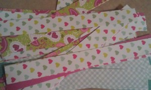 """Cut your paper into strips approximately 1"""" wide.  Glue two strips with the white sides together so that you end up with two different patterns on each strip."""