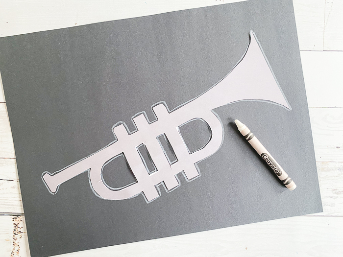 Outline a jazz instrument on black construction paper